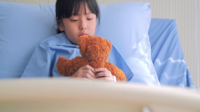 babymädchen in stimmungsvolle traurig sitzt auf dem bett im krankenhaus und teddy-bär allein zu betrachten. stressigen momente - waisenhaus stock-videos und b-roll-filmmaterial