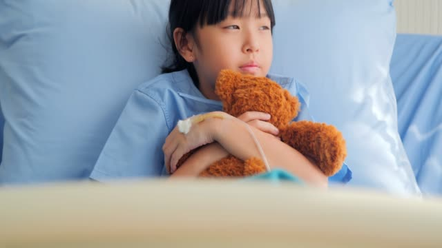 baby girl in moody sad sitting on the bed in hospital and looking at teddy bear alone .medical system in china & hong kong stressful moments - hospital stock videos & royalty-free footage