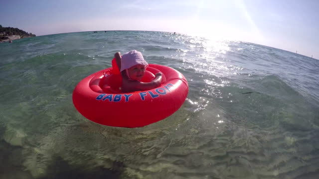 スイミング チューブ - 水泳、リラックス、日光浴 - 海の水で初めての女の赤ちゃん - 女の赤ちゃん点の映像素材/bロール