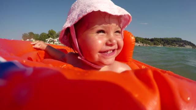 baby girl in swimming tube - swimming , relaxing , sunbathing - first time in sea water - sunbathing stock videos and b-roll footage