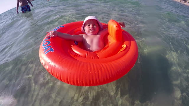 baby girl in swimming tube - swimming , relaxing , sunbathing - first time in sea water - genderblend stock videos & royalty-free footage