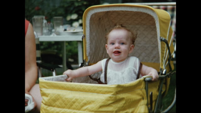 stockvideo's en b-roll-footage met 1955 ms baby girl (12 months) in yellow baby carriage, making funny faces with tongue / toronto, canada - 1955