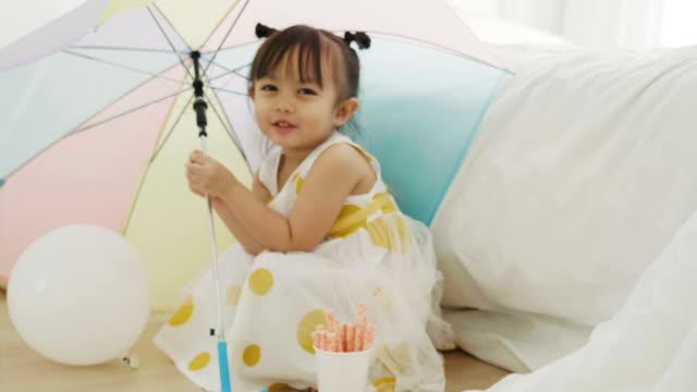 女の赤ちゃんは、パステル カラーの傘を保持しています。 - 片付いた部屋点の映像素材/bロール
