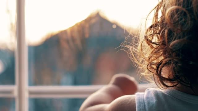 vídeos de stock e filmes b-roll de baby girl is looking out the window - bebés meninas