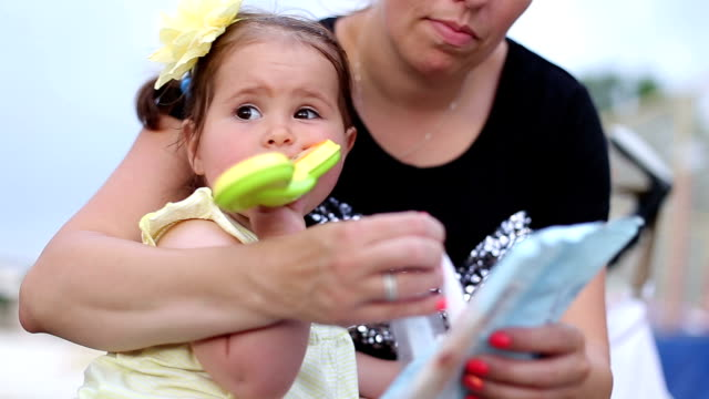 baby girl is sitting in her mother lap and chewing mobile phone teether - wet wipe stock videos & royalty-free footage