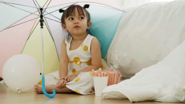 女の赤ちゃんは傘の下で座っています。 - 片付いた部屋点の映像素材/bロール