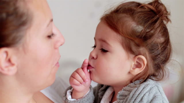 baby girl is sucking her thumb and watching her mother chewing bubble gum - gomma da masticare video stock e b–roll