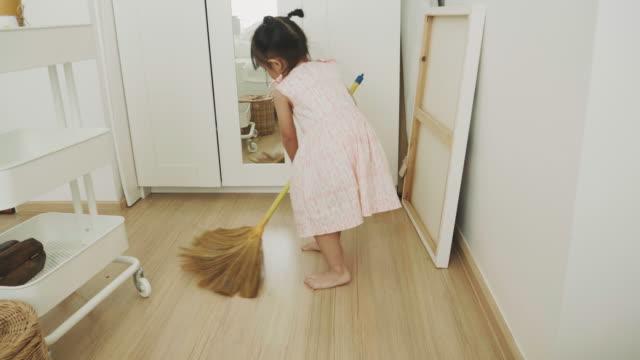 vídeos de stock e filmes b-roll de baby girl is sweeping floor - trabalho doméstico