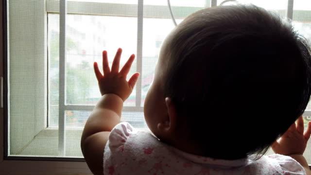女の赤ちゃんが窓をノックして見ている - 窓越し点の映像素材/bロール