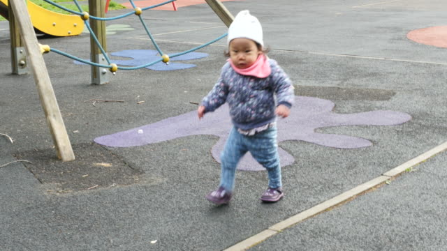 baby girl learning walk in the playground - one baby girl only stock videos & royalty-free footage