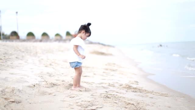 砂浜のビーチで散歩を学ぶ女の赤ちゃん - 手持ち撮影点の映像素材/bロール