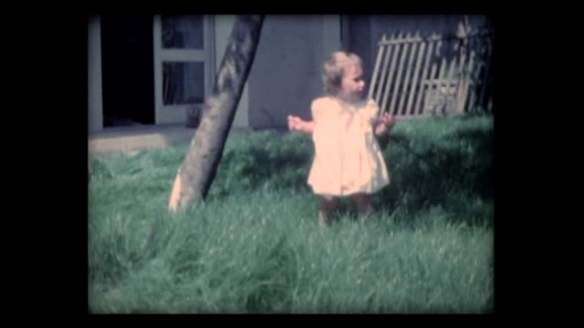 1962 baby girl learns to walk in tall grass - primi passi video stock e b–roll