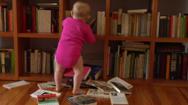 ws baby girl (12-17 months) littered books out from bookshelf / berlin, germany - unordentlich stock-videos und b-roll-filmmaterial