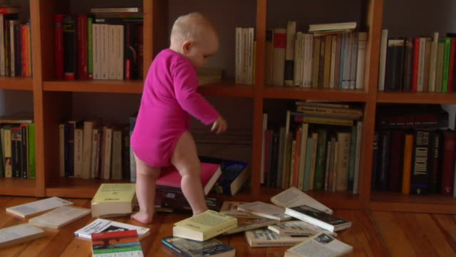vídeos de stock, filmes e b-roll de ws baby girl (12-17 months) littered books out from bookshelf / berlin, germany - esetante de livro