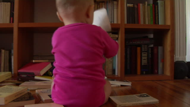 vídeos de stock, filmes e b-roll de ms pan baby girl (12-17 months) littered books out from bookshelf / berlin, germany - esetante de livro