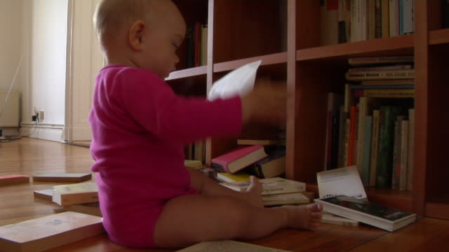 cu baby girl (12-17 months) littered books out from bookshelf / berlin, germany - 12 17 months stock videos & royalty-free footage
