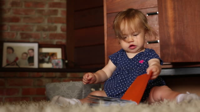 stockvideo's en b-roll-footage met a baby girl looking at a book inside of her home. - stippen