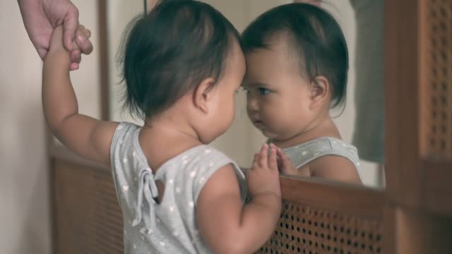 baby girl looking at herself on mirror - mirror stock videos & royalty-free footage