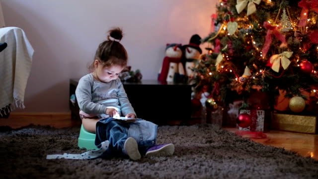 Baby girl looking at smart phone and sitting on a potty near a Christmas tree