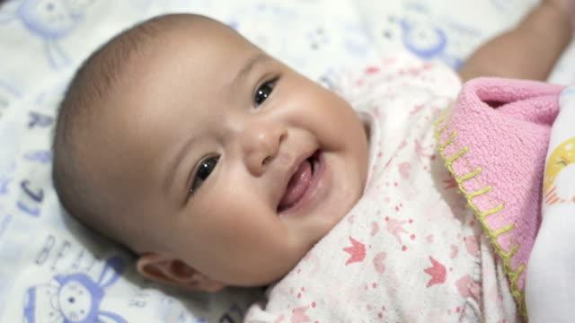 baby girl lying down smiling. - camera dei bambini video stock e b–roll