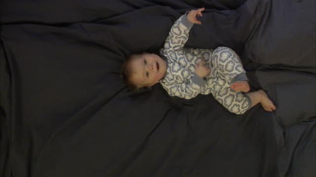 vídeos de stock e filmes b-roll de baby girl lying in a bed, sweden. - olhar de lado