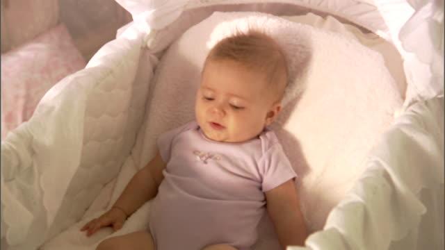 vídeos de stock e filmes b-roll de cu, zi, baby girl (6-9 months) lying in basinet, laughing - 6 11 meses
