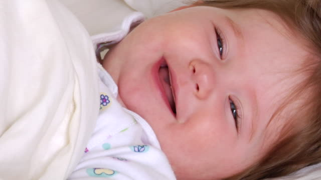 cu baby girl lying in bed and closing her eyes/ vancouver, bc - babygro stock videos & royalty-free footage