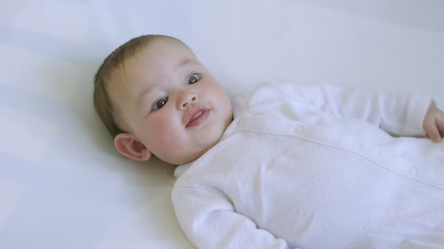 baby girl lying in her crib. - weibliches baby stock-videos und b-roll-filmmaterial