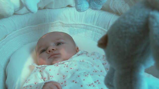 cu td tu baby girl (2-5 months) lying in moses basket watching toy mobile turning over her head, brussels, belgium - テディベア点の映像素材/bロール
