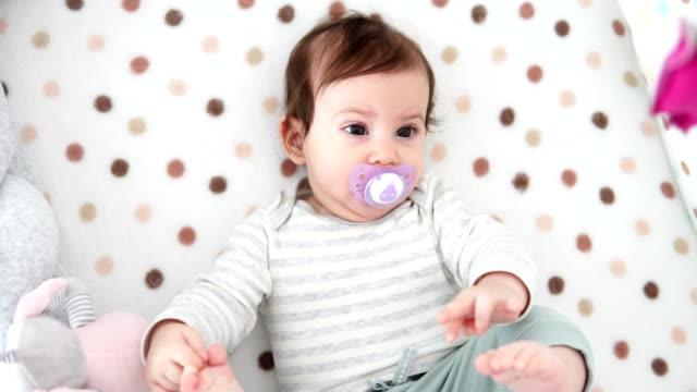 stockvideo's en b-roll-footage met het meisje dat van de baby op rug in voederbak ligt, die door zich speelt - alleen baby's