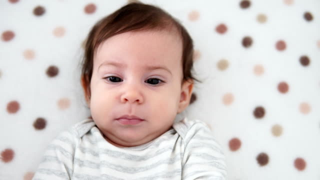 stockvideo's en b-roll-footage met het meisje dat van de baby op rug in voederbak ligt, die door zich speelt - wieg