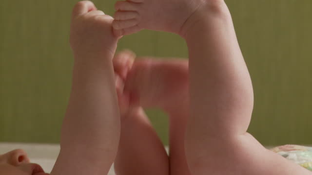 slo mo cu baby girl lying on back, touching toe / atlanta, georgia, usa - toe stock videos & royalty-free footage