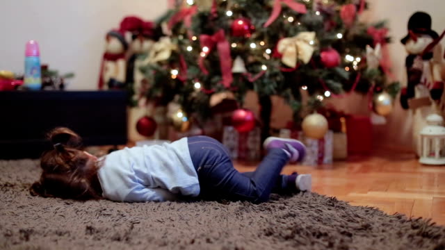 baby girl lying on the floor in front of christmas tree and sulking , she is tired - baby girls stock videos & royalty-free footage