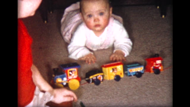 1957 baby girl on floor with toy train