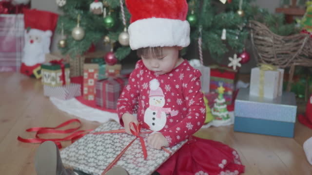 vidéos et rushes de petite fille en ouvrant la boîte de cadeau en face de l'arbre de noël à la maison - un seul bébé fille
