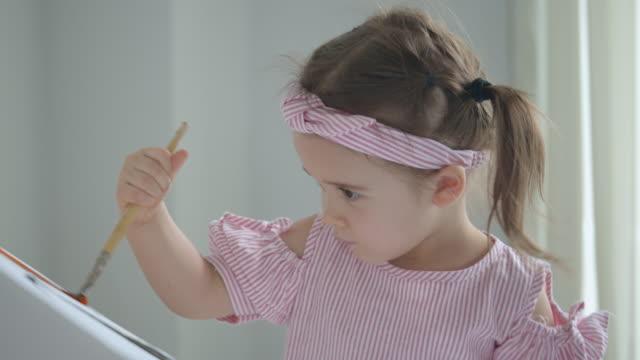 baby-mädchen malerei das spielzeughaus im wohnzimmer zu hause. - haarschmuck stock-videos und b-roll-filmmaterial