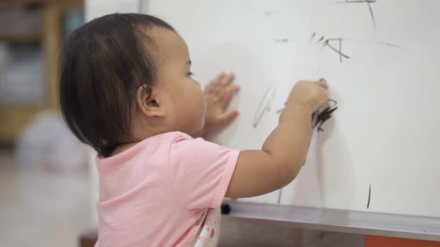 vídeos de stock e filmes b-roll de baby girl painting whiteboard - infantário