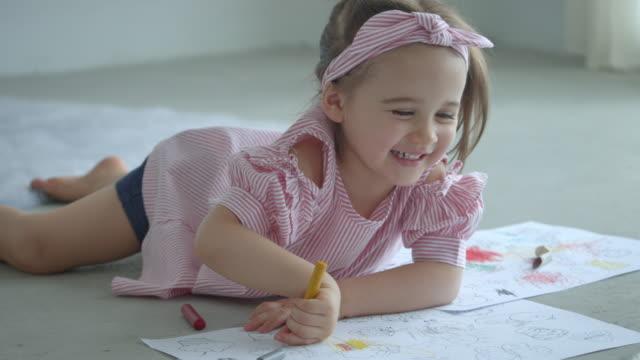 baby-mädchen-malerei mit kreide im wohnzimmer zu hause. - haarschmuck stock-videos und b-roll-filmmaterial