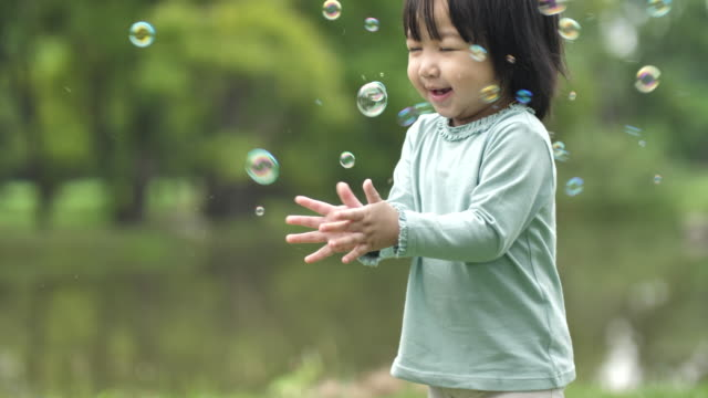 baby girl play bubbles at spring garden - bubble wand stock videos & royalty-free footage