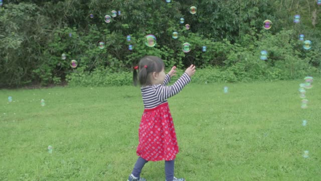 baby girl play bubbles at spring garden