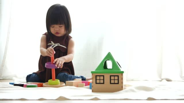 女の赤ちゃんは自宅で食べ物のおもちゃのふりをする - おもちゃ点の映像素材/bロール