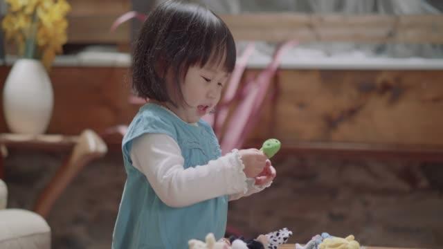 vidéos et rushes de bébé fille jeu marionnettes à la maison - un seul bébé fille