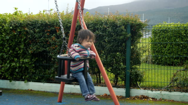 baby girl play swing in playground