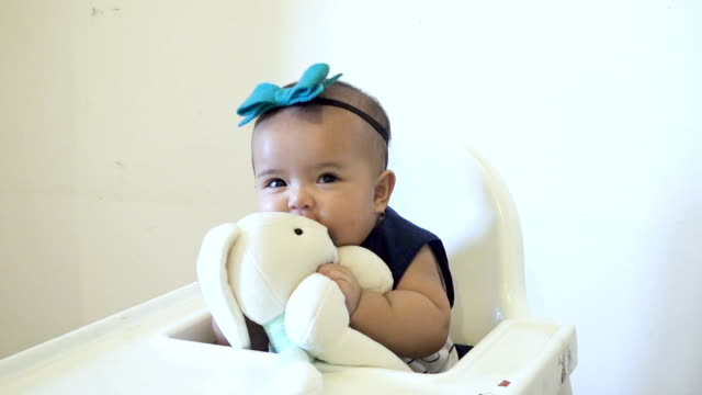 Baby girl playing and cuddling rabbit doll on high chair