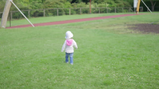baby girl playing at outside playground - natural parkland stock videos and b-roll footage