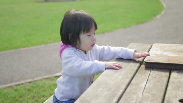 baby girl playing at outside playground - picnic table stock videos & royalty-free footage