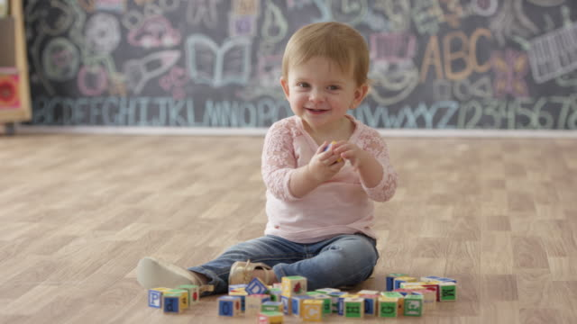 baby girl playing at preschool - sitting on floor stock videos & royalty-free footage
