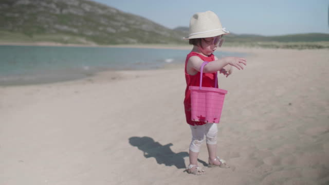 baby girl playing at summer beach,donegal,ireland - bucket stock videos & royalty-free footage