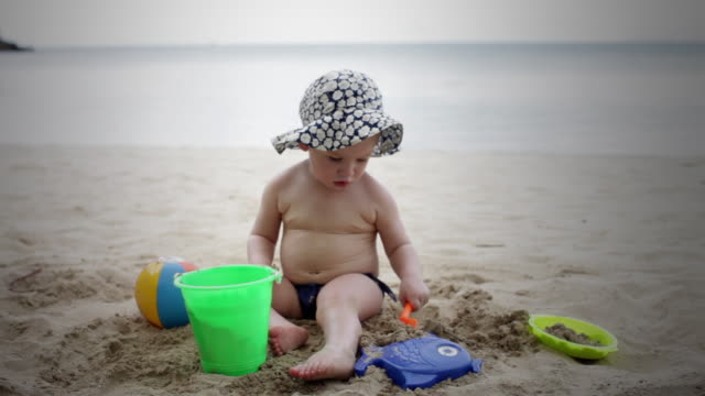 ws baby girl (18-23 months) playing in sand with shovel and bucket on beach, woman walking in background / st marys, antigua, antigua and barbuda - 18 23 months stock videos & royalty-free footage