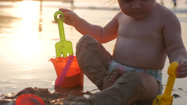 Baby girl playing in the sand near the sea shore